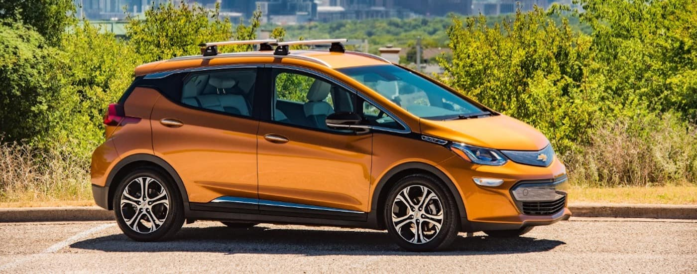 An orange 2017 Chevy Bolt is parked in front of bushes.