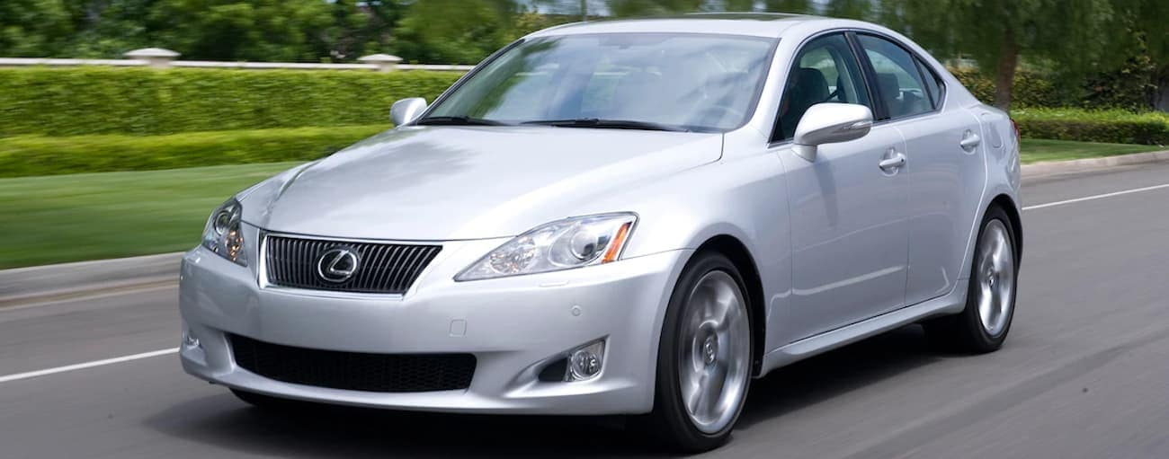 A silver 2009 Used Lexus IS is driving in front of a lawn and hedges near Cincinnati, OH.