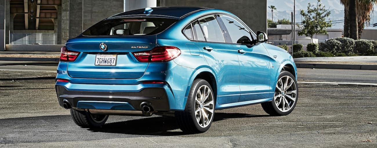 A blue 2016 used BMW X4 m40i is parked under a highway in Cincinnati, OH.