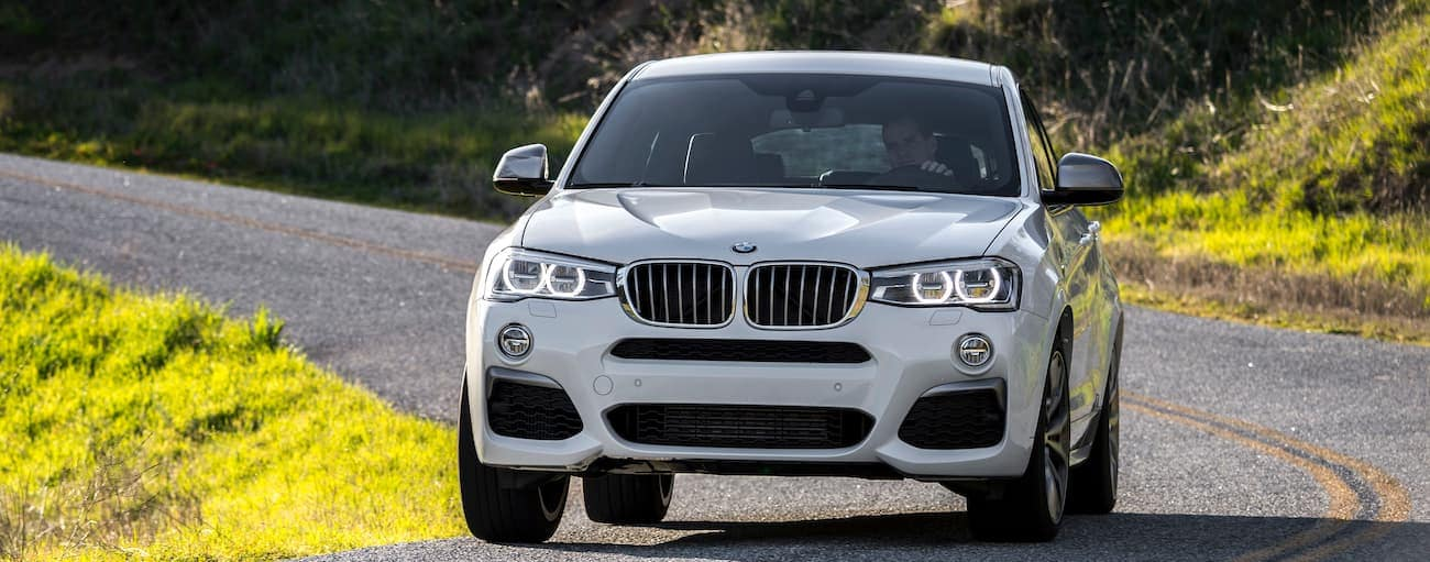 A white 2016 used BMW X4 is driving around a corner outside Cincinnati, OH.