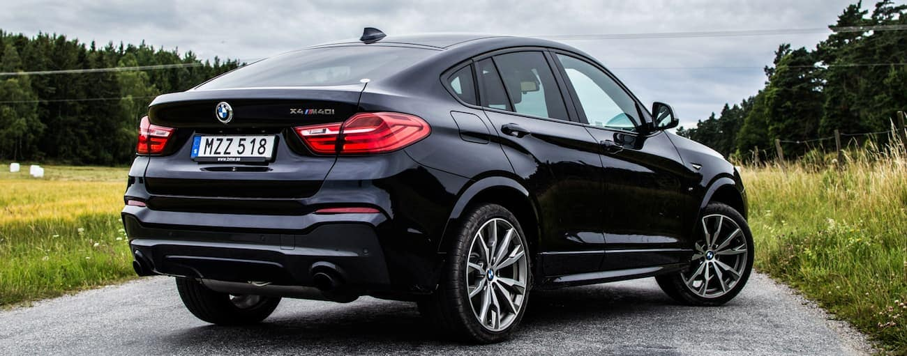 A black used BMW X4 is parked on a narrow road outside Cincinnati, OH.