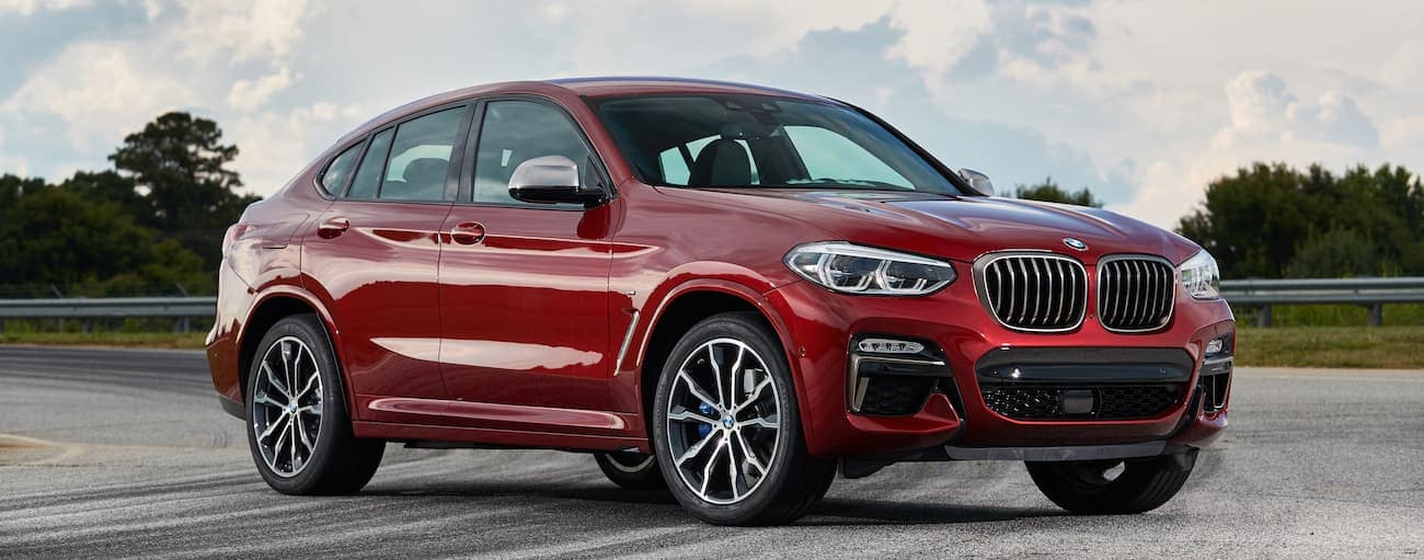 A red 2018 used BMW X4 is parked on a corner with a guard rail and skid marks outside Cincinnati, OH.