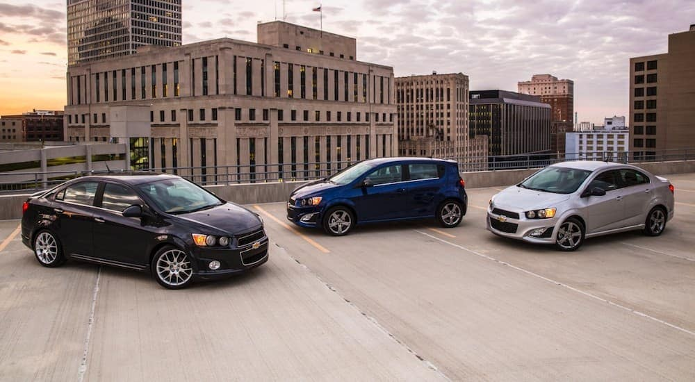 Three 2016 Chevy Sonics are on a rooftop parking garage. Check them out and compare used car values in Cincinnati, OH.