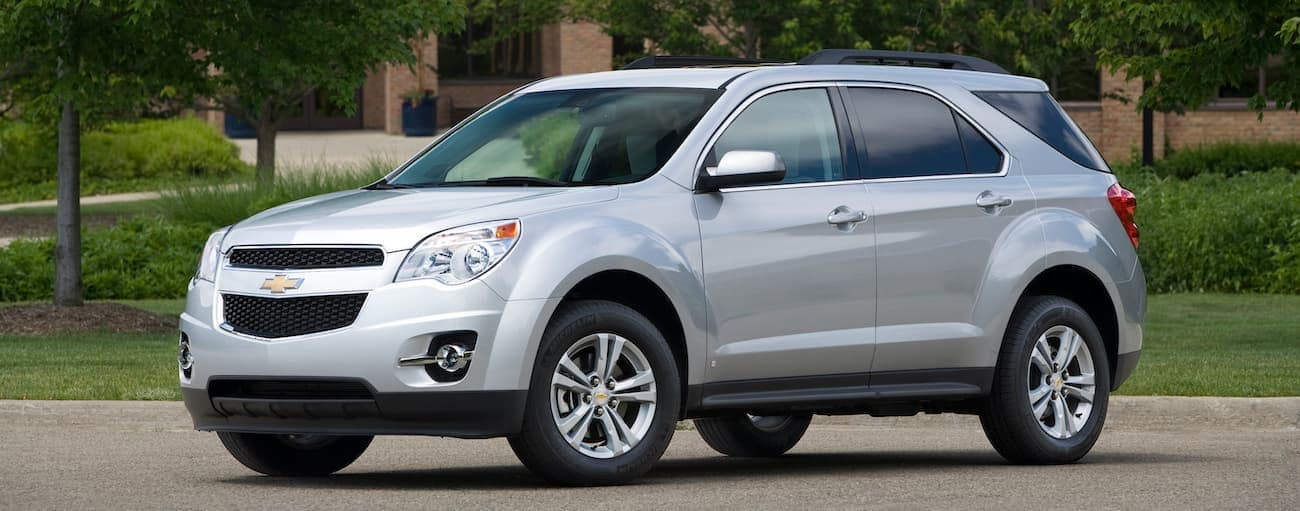 A silver 2010 used Chevy Equinox is parked outside a Cincinnati, OH building.