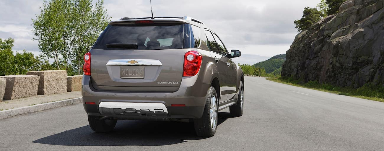 A beige 2013 used Chevy Equinox is driving up a rock lined road. Check one out a Cincinnati, OH dealership.