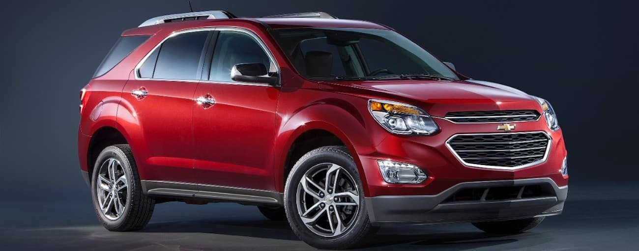 A red 2016 used Chevy Equinox is on a dark background. Check one out in Cincinnati, OH.