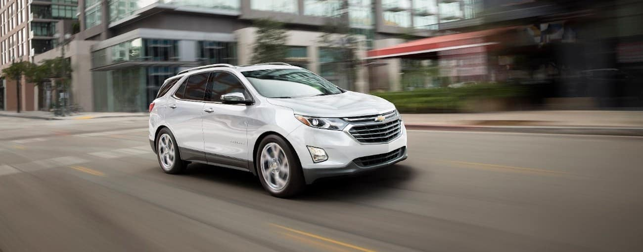 A white 2019 used Chevy Equinox is driving downtown in Cincinnati, OH.