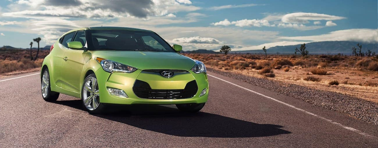 A lime green 2012 used Hyundai Veloster is parked in the desert.