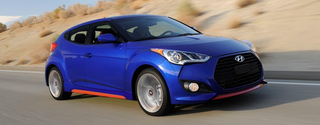 A blue 2015 used Hyundai Veloster is driving in front of a blurred sandy hill outside Cincinnati, OH.