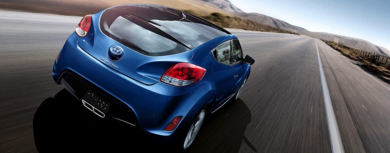 A blue 2017 used Hyundai Veloster is driving away on a straight road.