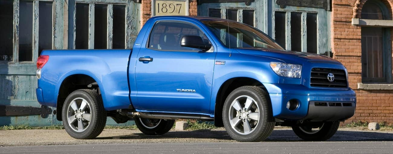 A blue 2007 Toyota Tundra single cab is in front of a very old brick building.