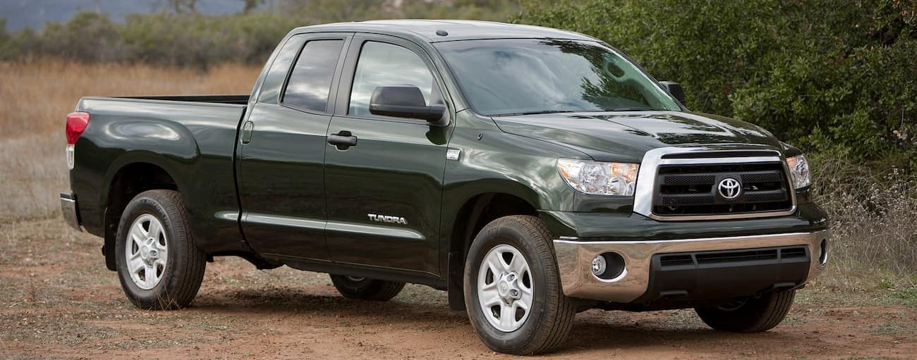 A green 2010 used Toyota Tundra is parked in the dirt in front of trees outside Cincinnati, OH.