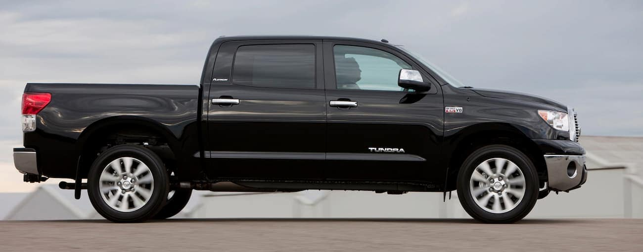 A black 2013 used Toyota Tundra is driving past white buildings.
