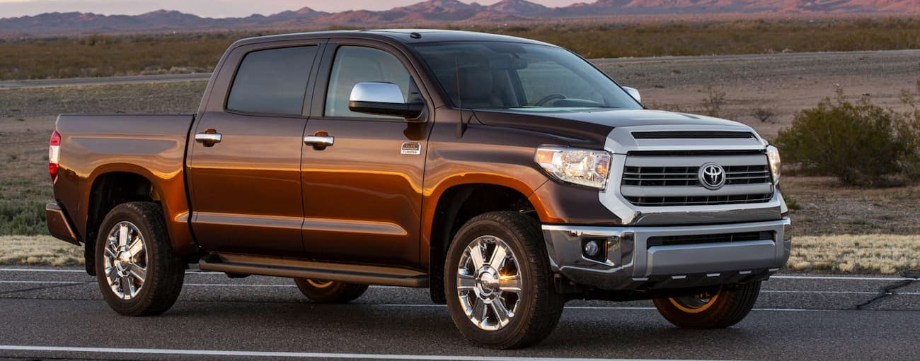 A brown 2014 used Toyota Tundra is parked on a road with mountains and a sunset in the distance.