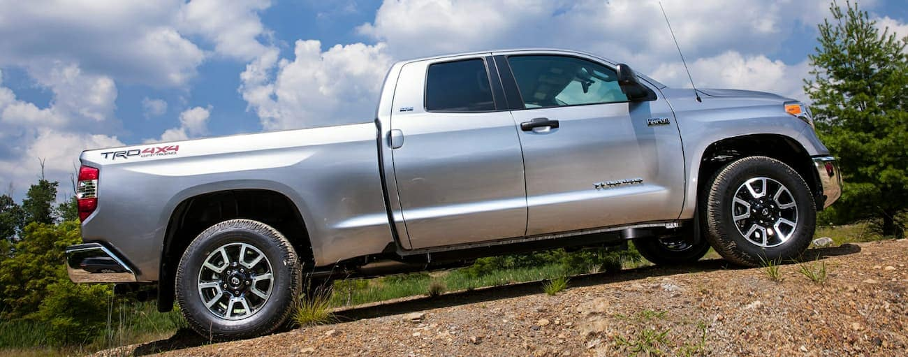 A silver 2015 used Toyota Tundra is climbing a dirt hill.