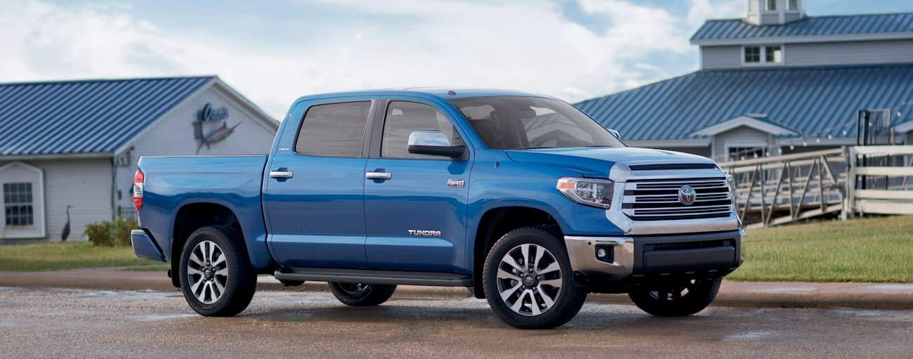 A blue 2018 Toyota Tundra is parked in front of buildings with blue roofs.