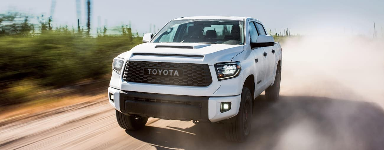 A white 2019 Toyota Tundra TRD Pro is driving on a dusty dirt road.