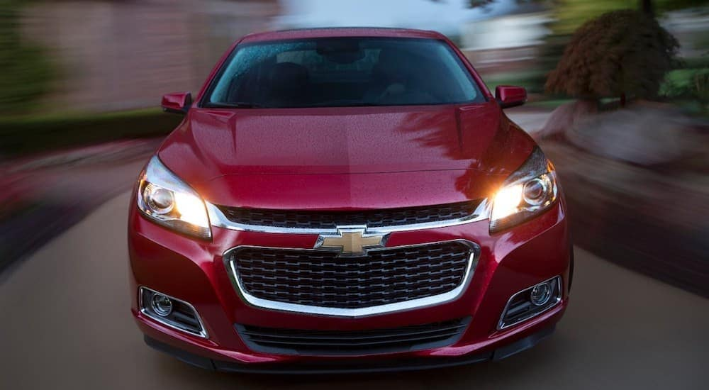 A red 2015 Chevrolet Malibu is driving fast down a road after leaving a buy here pay here Louisville dealership