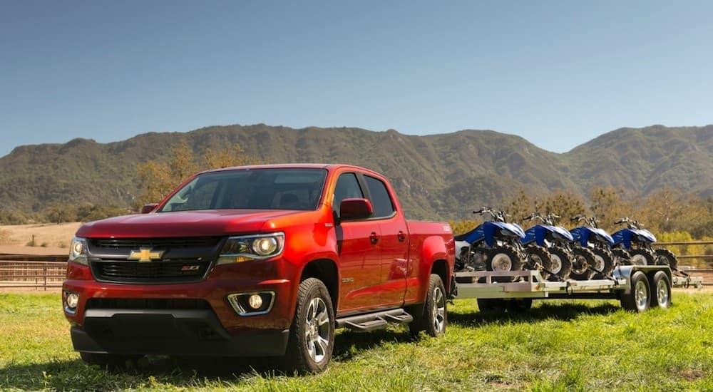A red Chevy Colorado is towing a trailer with atvs in a field.