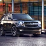 A black Chevy Tahoe, which is popular among used cars in Dayton, Ohio, is parked in front of a building at dusk.