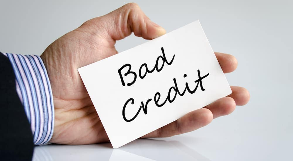 'Bad Credit' is written on a card in someone's hand.