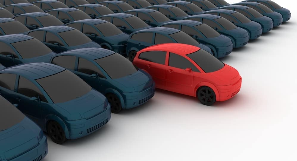 There is one red car in front of rows of black cars.