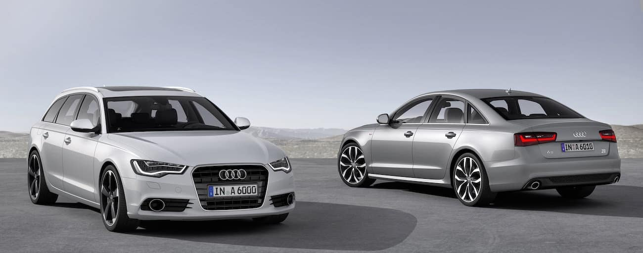 A silver and a white 2014 used Audi A6 are parked in an open area.