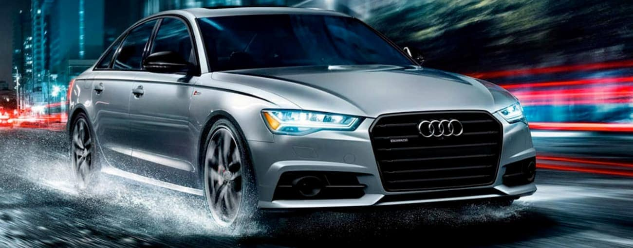 A silver 2017 used Audi A6 is driving in the rain at night in Cincinnati, OH.