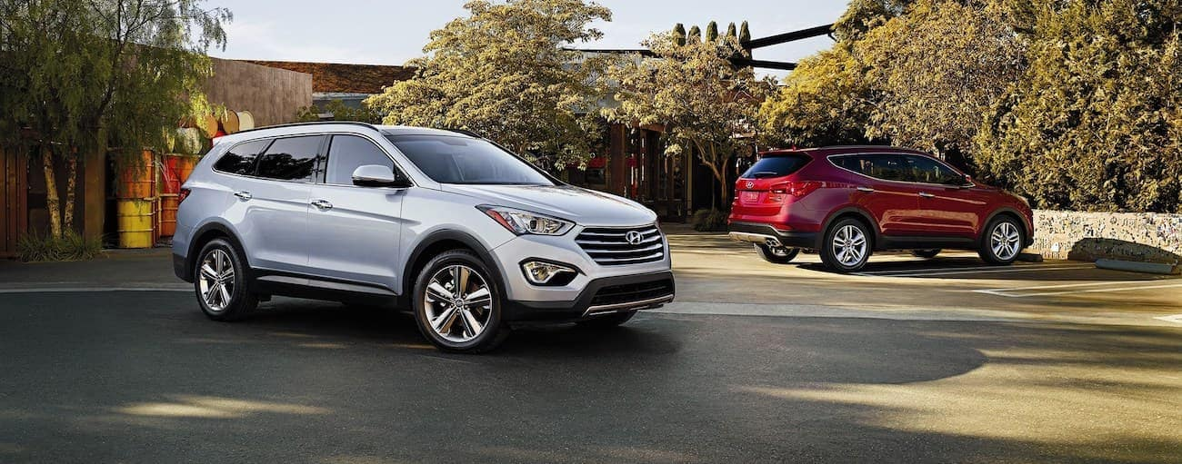 A silver 2016 used Hyundai Santa Fe Sport is parked next to a red one in a driveway outside Cincinnati, OH.