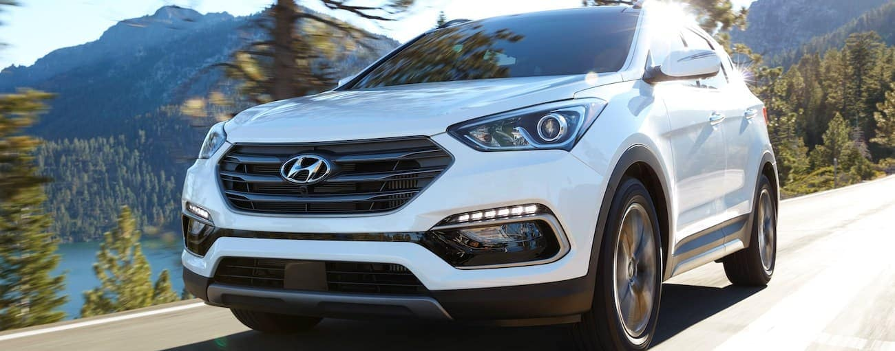 A white 2018 used Hyundai Santa Fe Sportis driving with mountains behind it.
