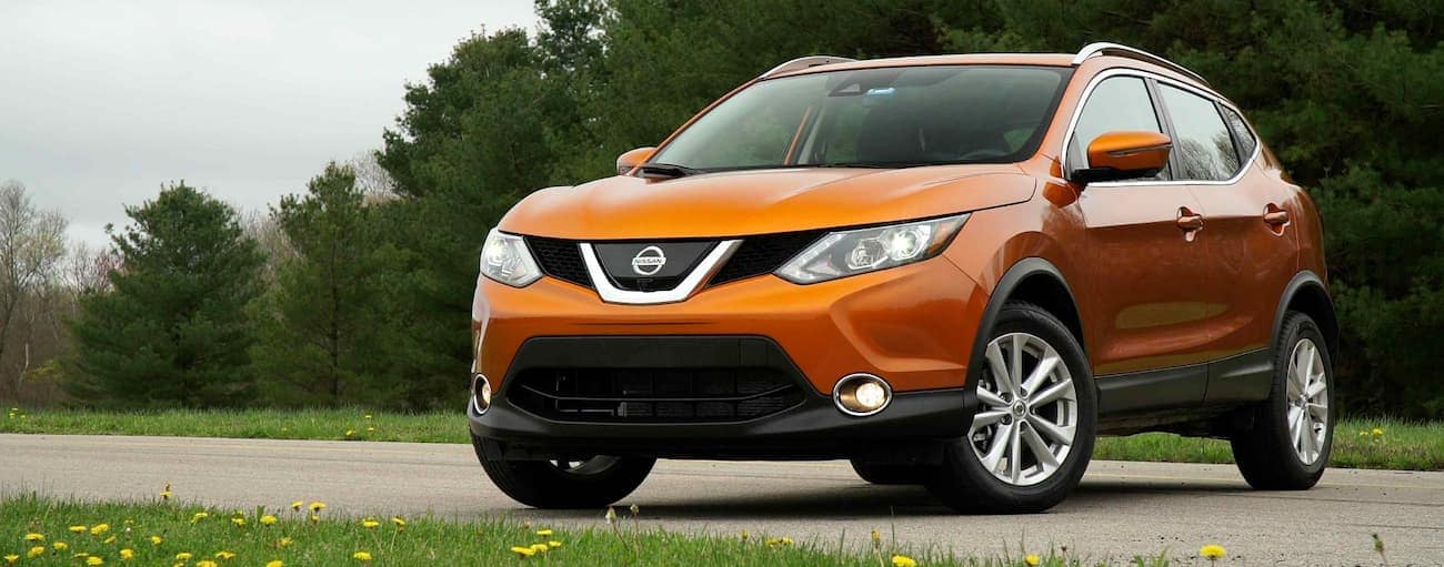 An orange 2017 Nissan Rogue Sport is parked in front of trees outside Cincinnati, OH.