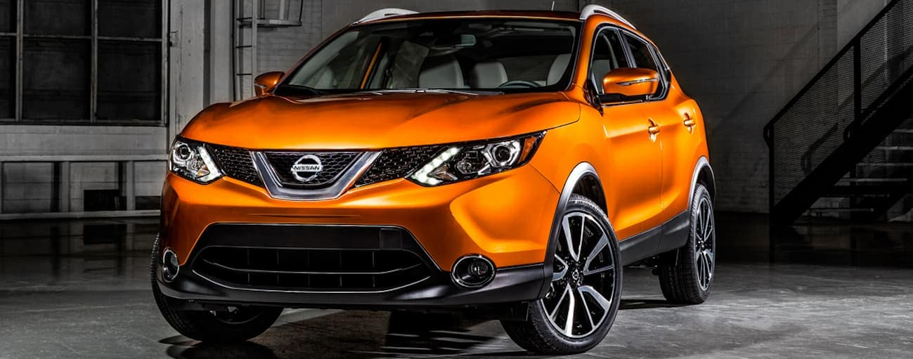 An orange 2018 Nissan Rogue Sport with black accents is parked in a warehouse.