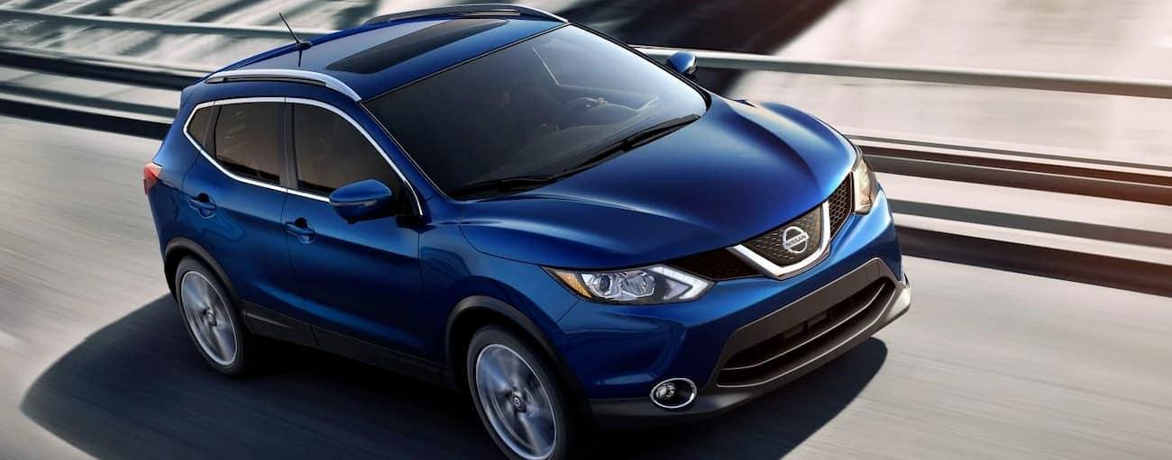 A blue 2019 Nissan Rogue Sport is driving on a highway near Cincinnati, OH.