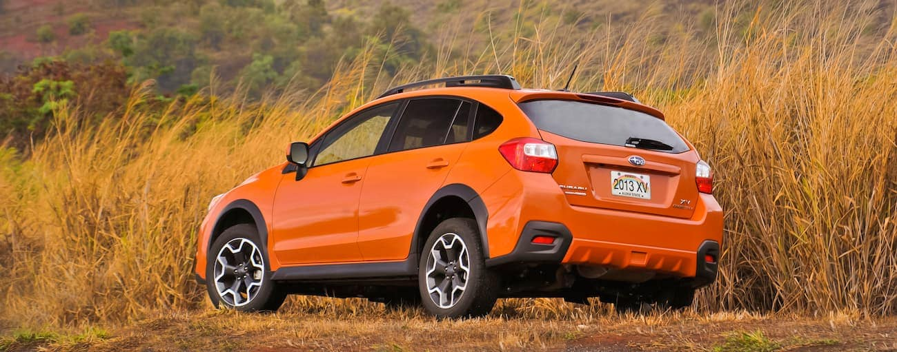 An orange 2013 used Subaru Crosstrek is parked in a field in Hawaii.
