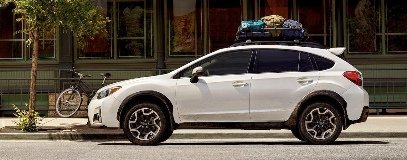 A white 2016 used Subaru Crosstrek is parked on a side street in Cincinnati, OH with items on the roof rack.