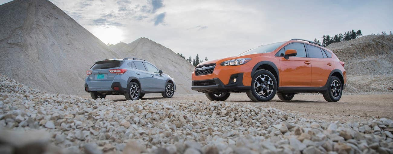 A blue 2018 used Subaru Crosstrek is parked next to an orange one in a gravel pit.