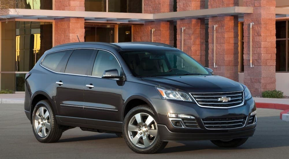 2015 Chevy Traverse LTZ is parked on pavement in front of a brown building.