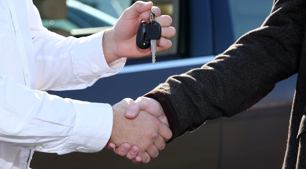 A man is shaking hands with a salesman at a used car dealership in Dayton, Ohio