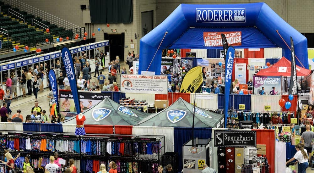 The Air Force Marathon in Dayton, Ohio Fitness Expo, thousands of people are working around a school gym.
