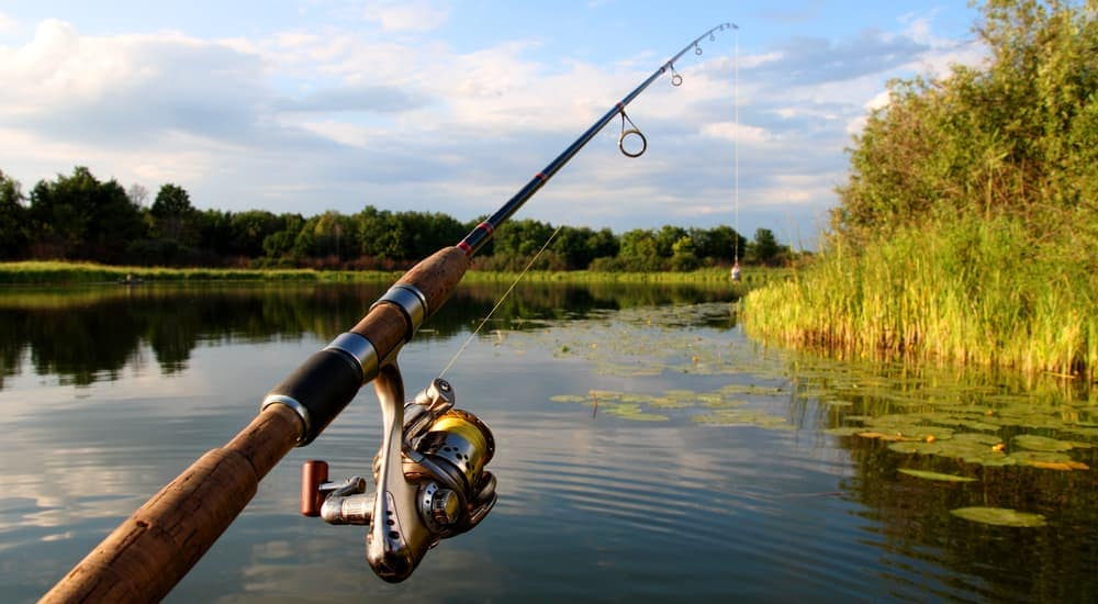 A fishing pole is shown over the water of a lake.