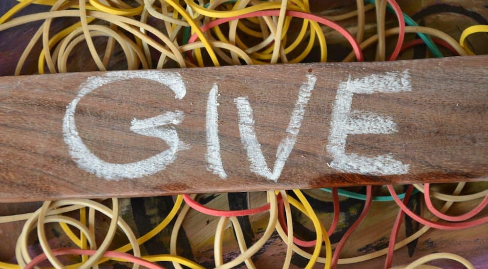'Give' written on a piece of wood with chalk, Crafted - Food, Beer, and Music Festival.