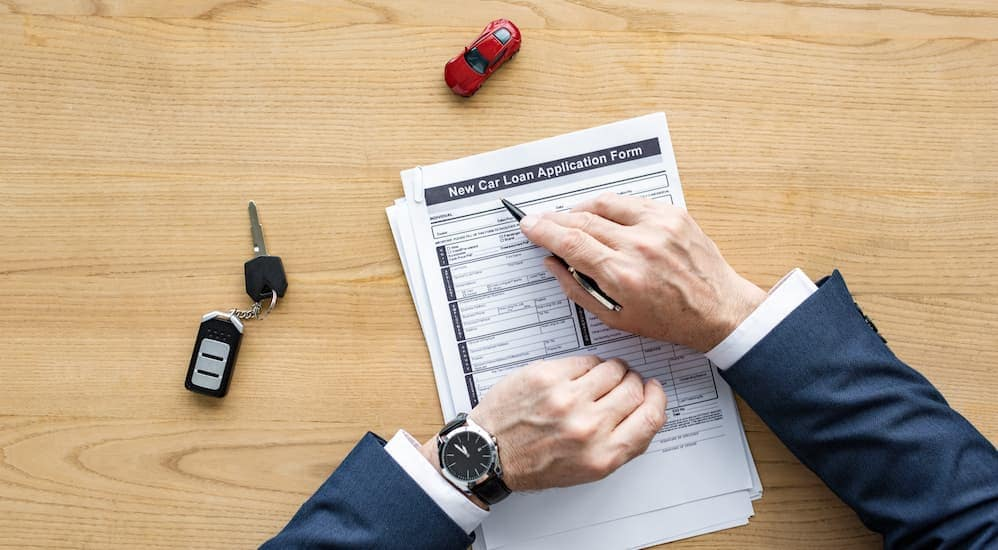 A man filling out a new car loan application on a table at a buy here pay here Louisville Dealership with toy car and car keys on table