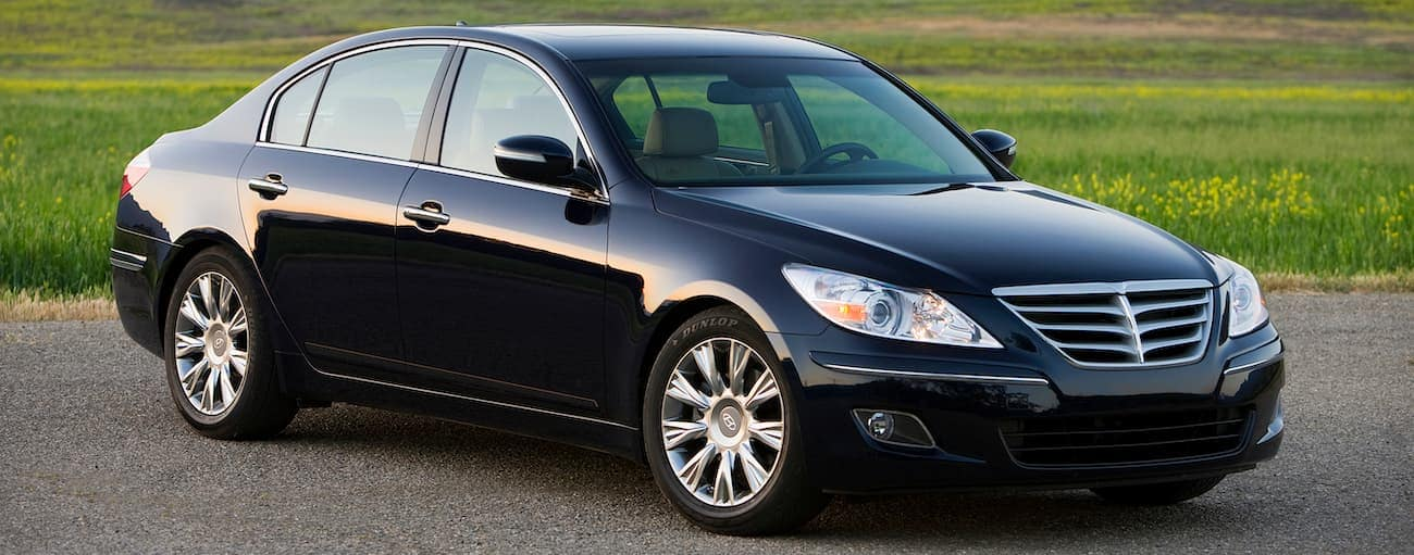 A black used 2011 Hyundai Genesis is parked in front of grass near Cincinnati, OH