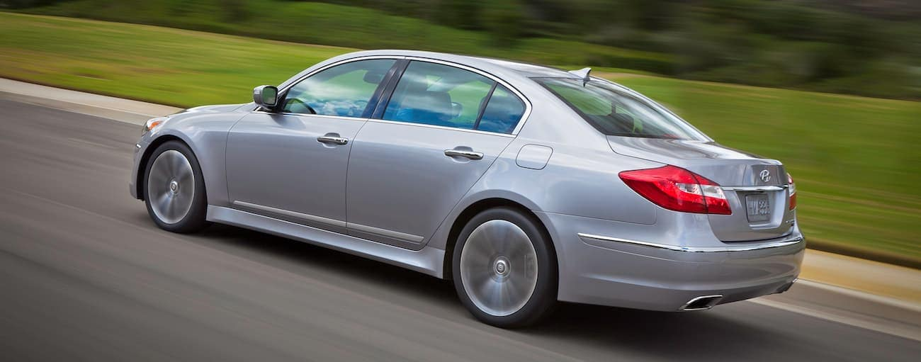 A silver 2013 used Hyundai Genesis is driving quickly on a grass-lined road.