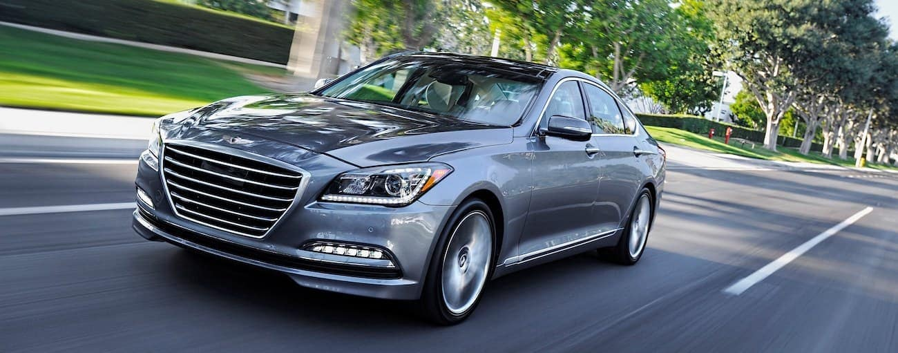 A grey used 2016 Hyundai Genesis is driving through a neighborhood near Cincinnati, OH
