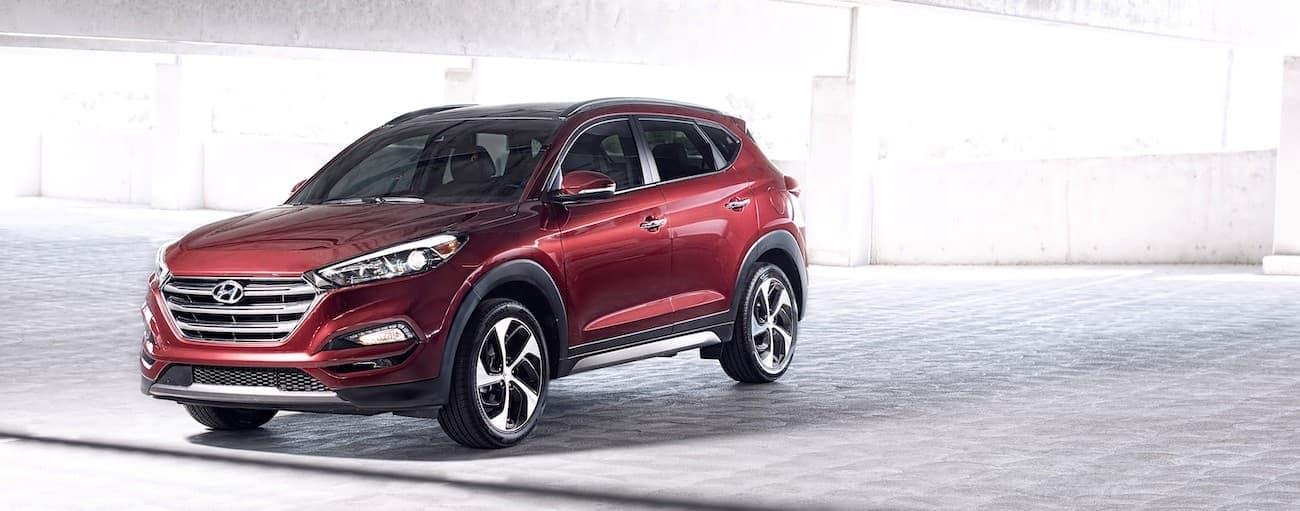 A red 2016 used Hyundai Tucson is in a bright parking garage near Cincinnati, OH.