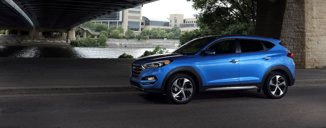 A blue 2017 used Hyundai Tucson is parked under an overpass.