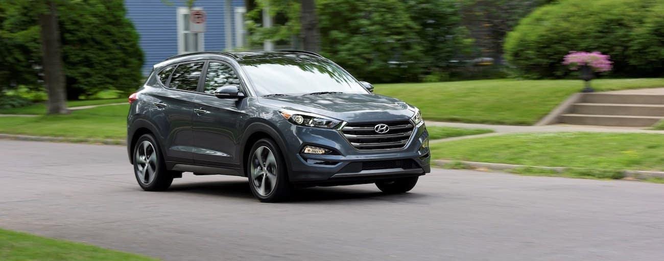A grey 2018 used Hyundai Tucson is driving through a suburban neighborhood.