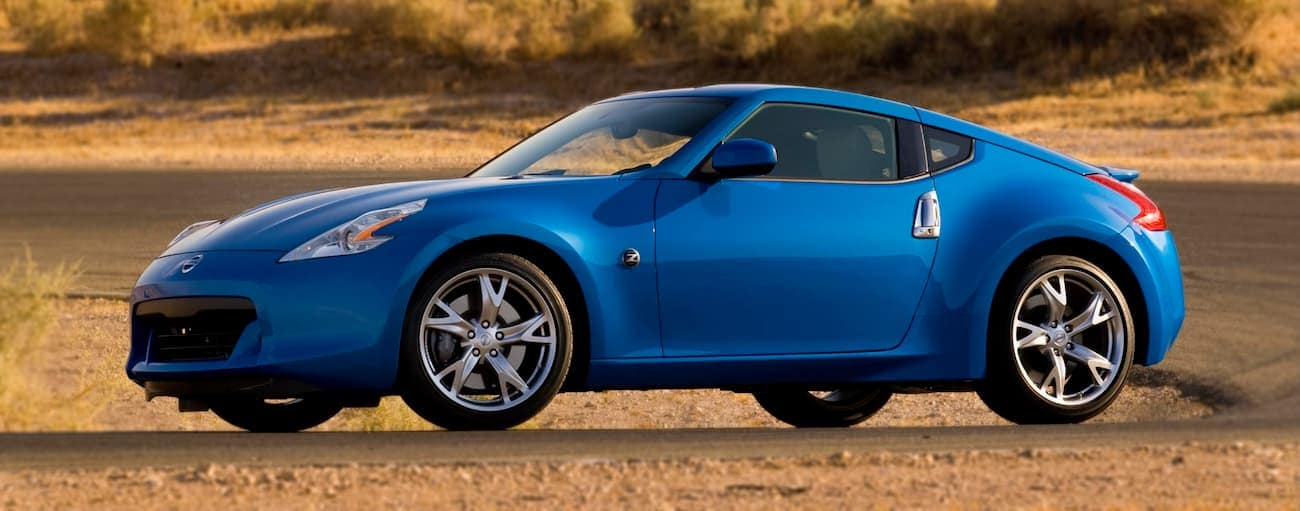 A blue 2009 used Nissan 370Z on a dirt track