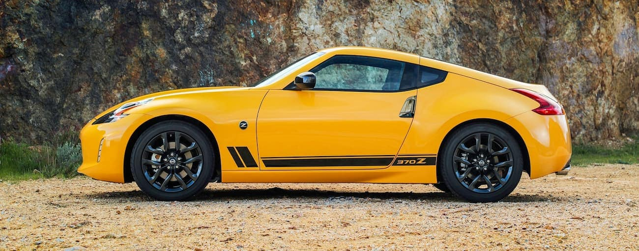 A yellow 2018 used Nissan 370Z is parked in front of a rock cliff.